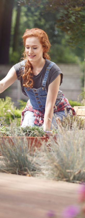 Woman pursuing a gardening career, working on a sunny wooden terrace
